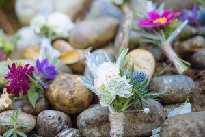 Beautiful wedding buttonholes on pebbles
